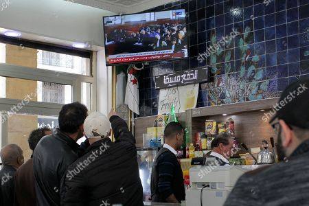 People watch the trial of former Algerian Prime Ministers Ahmed Ouyahia and Abdelmalek Sellal, in a cafe of Algiers, Wednesday, Dec.4, 2019. Ahmed Ouyahia, who was forced out as prime minister in March as protests against President Abdelaziz Bouteflika escalated, and his predecessor Abdelmalek Sellal, are facing questions Wednesday and face corruption charges
