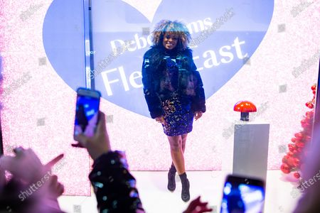 Stock Picture of Fleur East presses the button to switch on the stores Christmas lights