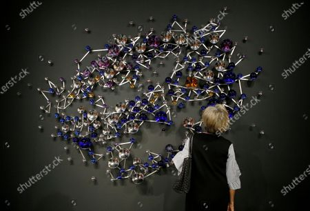 An Art Basel patron looks at a sculpture by Danish-Icelandic artist Olafur Eliasson during Art Basel in Miami, Florida, USA, 04 December 2019. Art Basel represents over 250 art galleries onsite at the Miami Beach Convention Center and is considered one of the world's largest art festivals with art events throughout the city.