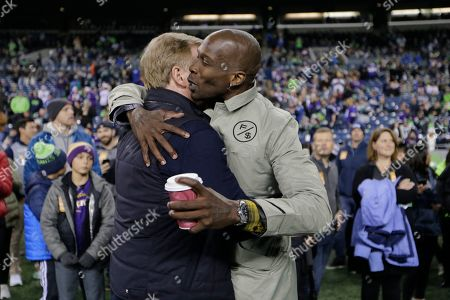 Former NFL football players Chad Ochocinco, right, hugs NFL Commissioner Roger Goodell, left, before an NFL football game between the Seattle Seahawks and the Minnesota Vikings, in Seattle