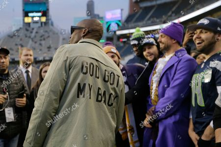 Former NFL football player Chad Ochocinco, left, stands on the sideline before an NFL football game between the Seattle Seahawks and the Minnesota Vikings, in Seattle