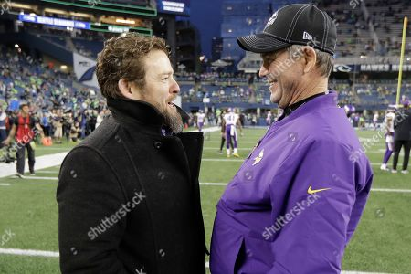 Seattle Seahawks general manager John Schneider, left, talks with Minnesota Vikings head coach Mike Zimmer, right, before an NFL football game, in Seattle