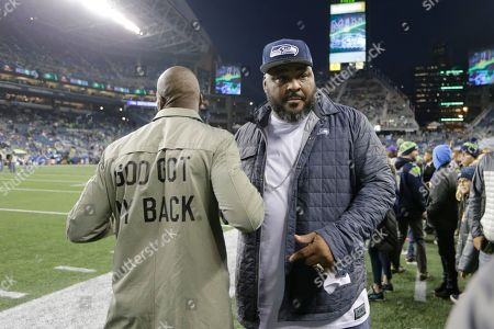 Former NFL football players Chad Ochocinco, left, and Walter Jones stand on the field before an NFL football game between the Seattle Seahawks and the Minnesota Vikings, in Seattle