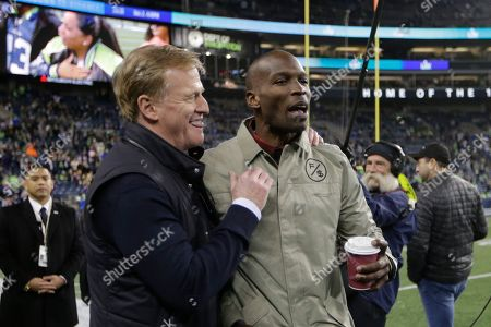 Former NFL football players Chad Ochocinco, right, stands with NFL Commissioner Roger Goodell, left, before an NFL football game between the Seattle Seahawks and the Minnesota Vikings, in Seattle