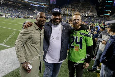 Former NFL football players Chad Ochocinco, left, and Walter Jones, center, pose for a photo with MLS soccer Seattle Sounders goalkeeper Stefan Frei, right, before an NFL football game between the Seattle Seahawks and the Minnesota Vikings, in Seattle