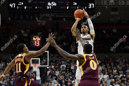 Connecticut's Tyler Polley shoots over Iona's Isaiah Washington, left, and Iona's Mo Thiam, right, in the second half of an NCAA college basketball game, in Storrs, Conn
