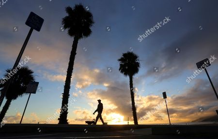 A person walks a dog on the beach path at sunset by the Pacific Ocean as the most recent in a series of storms passes through Southern California, seen from Will Rogers State Beach in the Pacific Palisades area of Los Angeles, . The storms brought several inches of rain and several feet of snow to mountain areas