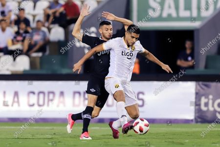Adrian Martinez (L) of Libertad vies for the ball with Hernan Lopes (R) of Guarani during the final of Copa Paraguay soccer tournament between Club Libertad and Club Guaraniat at Defensores del Chaco stadium in Asuncion, Paraguay, 04 December 2019.