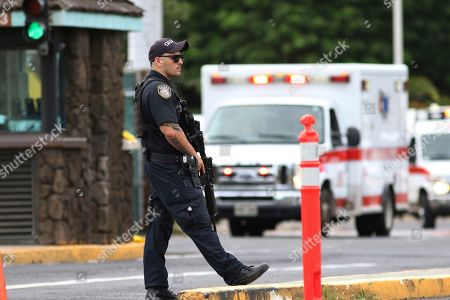Stock Photo of A security guard stands outside the main gate at Joint Base Pearl Harbor-Hickam, in Honolulu. A shooting at Pearl Harbor Naval Shipyard in Hawaii left at least one person injured Wednesday, military and hospital officials said. Joint Base Pearl Harbor-Hickam spokesman Charles Anthony confirmed that there was an active shooting at Pearl Harbor Naval Shipyard