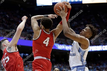 Ohio State guard Duane Washington Jr., center, and forward Kyle Young, left, struggle for possession of the ball with North Carolina forward Armando Bacot, right, during the first half of an NCAA college basketball game in Chapel Hill, N.C