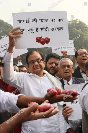 "Stock Picture of Indian lawmaker and former Finance Minister Palaniappan Chidambaram, center, holds a placard that reads ""Why is the Modi government silent on the rise of onion prices, participates in a protest against the rise in onion prices, outside the Indian parliament in New Delhi, India, . Chidambaram was released by an order from India's Supreme Court on Wednesday on bail in a case involving alleged bribery and money laundering benefitting his son's company"