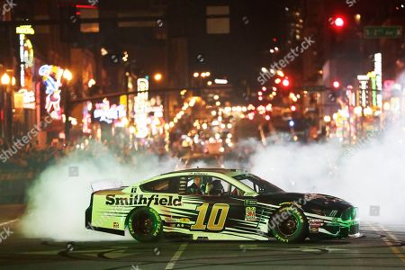 Aric Almirola does a burnout in the Burnouts on Broadway competition, during NASCAR Champion's Week in Nashville, Tenn