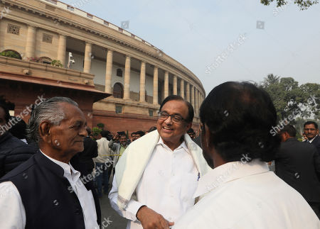 Indian lawmaker and former Finance Minister Palaniappan Chidambaram, center, talks to fellow lawmakers as he arrives at the Parliament House for a protest against the rise in onion prices, in New Delhi, India, . Chidambaram, just released on bail in a bribery case, has joined a protest of the government's economic policies, which are being blamed for India's slowest economic growth in six years