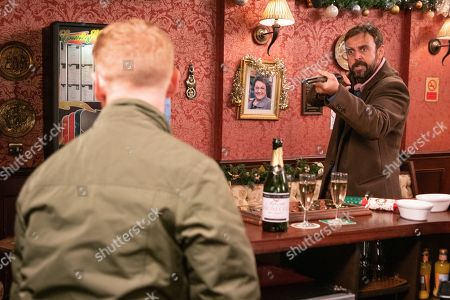 Stock Image of Ep 9961 & 9962 Christmas Day 2019 - Wed 25th Dec 2019 Following Gary Windass, as played by Mikey North, into the pub a worse-for-wear Derek Milligan, as played by Craige Els, lurches in looking for him, pulling out a gun and firing his first shot. As he points the gun at Gary, he runs from the pub and Derek gives chase into the Winter Wonderland.