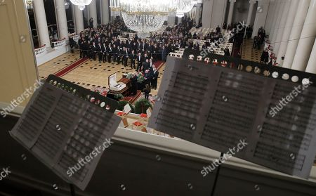 Stock Picture of Musicians pass by the coffin of Mariss Jansons during a memorial ceremony in the Great Philharmonic Hall in St.Petersburg, Russia, . Mariss Jansons, conductor of top classical ensembles including the Pittsburgh Symphony Orchestra and the Royal Concertgebouw Orchestra in Amsterdam, has died in Russia. He was 76