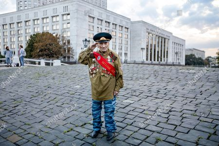 World War II veteran Lev Yatsevich, 92, salutes as he waits for other participants of an event marking the anniversary of the failed August 1991 hard-line coup outside the former Russian parliament building, which now houses the Russian Cabinet, in Moscow on . The coup, which briefly ousted Soviet leader Mikhail Gorbachev, precipitated the collapse of the Soviet Union