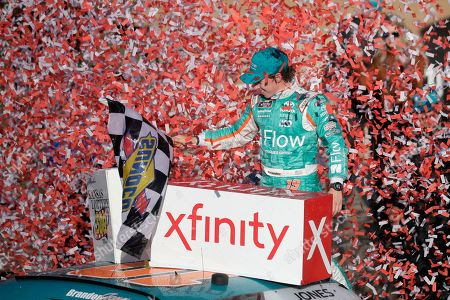 "Brandon Jones celebrates in Victory Lane after winning a NASCAR Xfinity Series auto race at Kansas Speedway in Kansas City, Kan. NASCAR has signed Busch Beer, Coca-Cola, Geico and Xfinity as its ""premier partners"" in a change to its traditional sponsorship model. The premier series starting next year will be known as the NASCAR Cup Series and not feature a title sponsor"