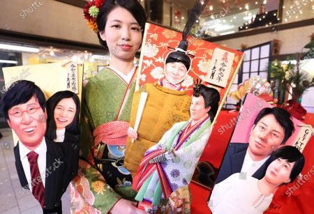 An employee of Japanese doll maker Kyugetsu displays ornamental wooden rackets 'hagoita' decorated with depiction of newly wed couple Shinjiro Koizumi and Christel Takigawa (R), Japanese Emperor Naruhito and Empress Masako (C) and newly wed couple Ryota Yamasato and Yu Aoi (L) for this year's news makers at the company's showroom.