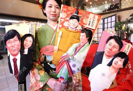 Stock Photo of An employee of Japanese doll maker Kyugetsu displays ornamental wooden rackets 'hagoita' decorated with depiction of newly wed couple Shinjiro Koizumi and Christel Takigawa (R), Japanese Emperor Naruhito and Empress Masako (C) and newly wed couple Ryota Yamasato and Yu Aoi (L) for this year's news makers at the company's showroom.