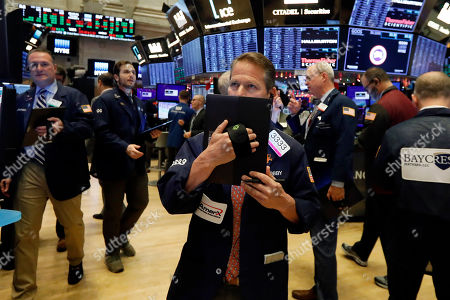 Stock Picture of Robert Charmak, center, works with fellow traders on the floor of the New York Stock Exchange, . Stocks are opening slightly higher on Wall Street led by technology companies and banks
