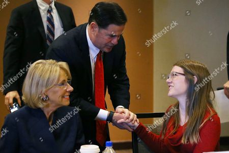 U.S. Education Secretary Betsy DeVos, left, joins Arizona Republican Gov. Doug Ducey, middle, as they talk with Grace Jones, a high school sophomore from Tucson, Ariz., after a roundtable discussion on school choice, in Scottsdale, Ariz. DeVos talked with state lawmakers, educators, students and parents about her $5 billion plan to fund tuition for private school students, prior to addressing the American Legislative Exchange Council