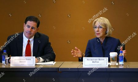 U.S. Education Secretary Betsy DeVos, right, joins Arizona Republican Gov. Doug Ducey, as they answer questions during a roundtable discussion on school choice, in Scottsdale, Ariz. DeVos talks with state lawmakers, educators, students and parents about her $5 billion plan to fund tuition for private school students, prior to addressing the American Legislative Exchange Council