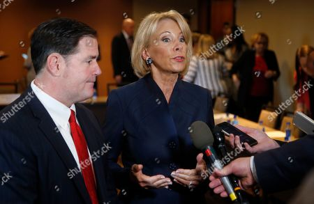 U.S. Education Secretary Betsy DeVos, right, joins Arizona Republican Gov. Doug Ducey, left, as they address the media after a roundtable discussion on school choice, in Scottsdale, Ariz. DeVos talks with state lawmakers, educators, students and parents about her $5 billion plan to fund tuition for private school students, prior to addressing the American Legislative Exchange Council