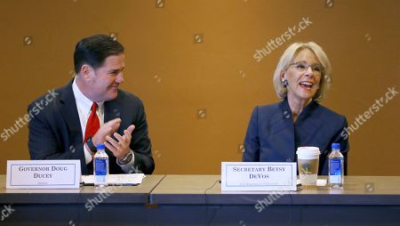 Stock Image of U.S. Education Secretary Betsy DeVos, right, smiles as she is applauded by Arizona Republican Gov. Doug Ducey, left, during a roundtable discussion on school choice, in Scottsdale, Ariz. DeVos talks with state lawmakers, educators, students and parents about her $5 billion plan to fund tuition for private school students, prior to addressing the American Legislative Exchange Council