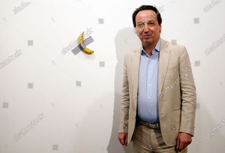 Stock Picture of Emmanuel Perrotin, founder of the Perrotin Gallery poses with Italian artist Maurizio Cattelan piece's 'Comedian' (a banana duct taped to the wall) during Art Basel in Miami, Florida, USA, 05 December 2019. Art Basel represents over 250 art galleries onsite at the Miami Beach Convention Center and is considered one of the world's largest art festivals with art events throughout the city.