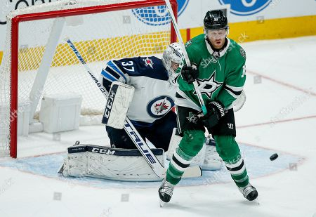 Stock Image of Dallas Stars forward Joe Pavelski (16) screens Winnipeg Jets goaltender Connor Hellebuyck (37), allowing forward Jamie Benn, not seen, to score during the first period of an NHL hockey game, in Dallas