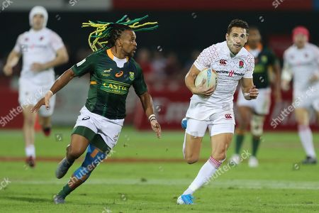 South Africa's Rosko Specman, left, tries to stop England's Ollie Lindsay-Hague during a match of the Emirates Airline Rugby Sevens in Dubai, United Arab Emirates, Friday, Dec.6, 2019