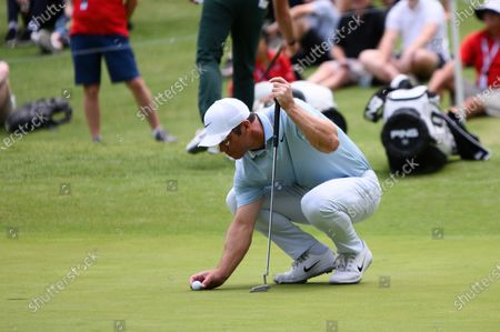 Paul Casey (ENG) places the ball