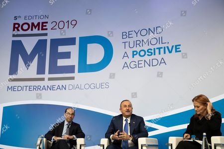Turkish Minister of Foreign Affairs Mevlut Cavusoglu, center, is flanked by Vice President of The German Mashall fund of the United States Ian Lesser, left, and CEO of RAICOM Monica Maggioni as he speaks at the Mediterranean dialogues conference in Rome