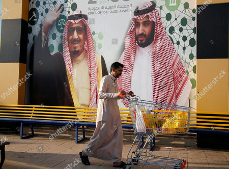 People walk past a banner showing walks past a banner showing Saudi King Salman, left, and Crown Prince Mohammed bin Salman, outside a mall in Jiddah, Saudi Arabia