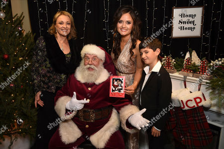 Stock Photo of Danica McKellar and her family cozy up with Santa at the world premiere of Christmas at Dollywood hosted by JCPenney and Hallmark Channel at Village East Cinema, in New York. The film debuts on the Hallmark Channel Sunday, Dec. 8 (8p.m. ET/PT, 7c