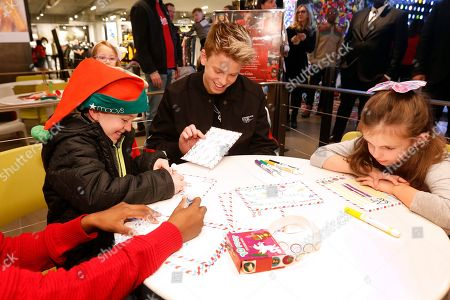 Carson Lueders, center, helps write letters to Santa on National Believe Day at Macy's Herald Square, in New York