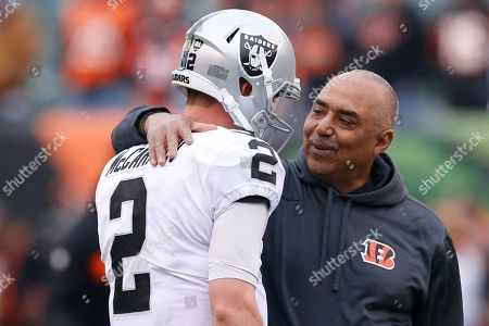 """Stock Picture of Shows then Cincinnati Bengals head coach Marvin Lewis, right, meeting with Oakland Raiders quarterback AJ McCarron (2) during warmups before an NFL football game in Cincinnati. In 2003, the NFL had three minority head coaches: future Pro Football Hall of Famer Tony Dungy, Herman Edwards and Lewis. In the 12 previous seasons, there had been six. Total. Considering that the majority of the players in the league 16 years ago were minorities, that imbalance was enormous. And disturbing. And, frankly, it was unfair. Paul Tagliabue, then the NFL commissioner, put together a committee that established the """"Rooney Rule,"""" which requires all teams with coaching and front office vacancies to interview minority candidates. The rule, long overdue, was named for Dan Rooney, then president of the Pittsburgh Steelers and the overseer of that committee"""