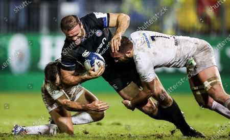 Bath vs ASM Clermont Auvergne. Bath's Jamie Roberts tackled by Morgan Parra and Alexandre Lapandry of Clermont