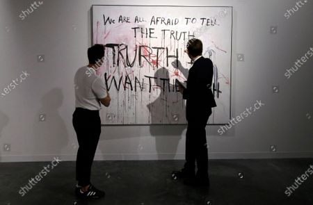 Patrons discuss a piece by British artist Tracey Emin during Art Basel in Miami, Florida, USA, 06 December 2019. Art Basel represents over 250 art galleries onsite at the Miami Beach Convention Center and is considered one of the world's largest art festivals with art events throughout the city.