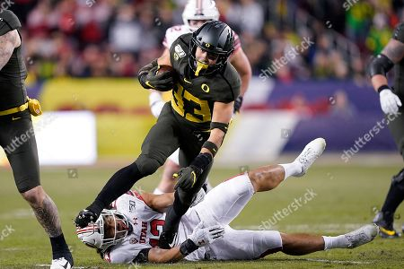 Oregon running back Cyrus Habibi-Likio (33) breaks a tackle by Utah linebacker Francis Bernard (13) during the first half of the Pac-12 Conference championship NCAA college football game in Santa Clara, Calif