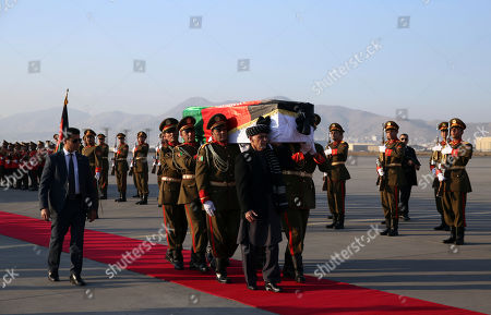 Afghan President Ashraf Ghani, foreground, and Afghan honor guards carry the coffin of Japanese physician Tetsu Nakamura during a ceremony before transporting his body to his homeland, at the Hamid Karzai International Airport in Kabul, Afghanistan, . Nakamura was killed earlier this week in a roadside shooting in eastern Afghanistan
