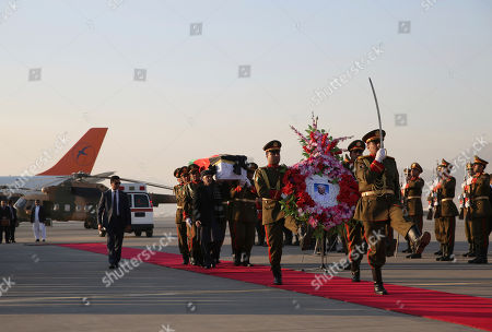 Afghan President Ashraf Ghani and Afghan honor guards carry the coffin of Japanese physician Tetsu Nakamura during a ceremony before transporting his body to his homeland, at the Hamid Karzai International Airport in Kabul, Afghanistan, . Nakamura was killed earlier this week in a roadside shooting in eastern Afghanistan