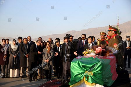 Afghan President Ashraf Ghani, speaks, next to the coffin of Japanese physician Tetsu Nakamura during a ceremony before transporting his body to his homeland, at the Hamid Karzai International Airport in Kabul, Afghanistan, . Nakamura was killed earlier this week in a roadside shooting in eastern Afghanistan