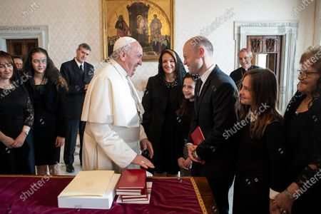 Stock Image of A handout picture provided by the Vatican Media shows Pope Francis (C) receiving Maltese Prime Minister Joseph Muscat during a private audience in Vatican City, 07 December 2019.