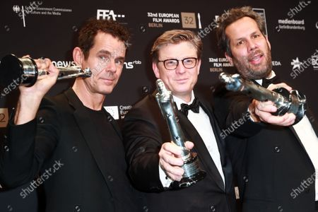 Tom Tykwer, Henk Handloegten and Achim von Borries pose with their European Achievement in Fiction Award during a photo-call after the 32nd European Film Awards ceremony in Berlin, Germany, 07 December 2019.