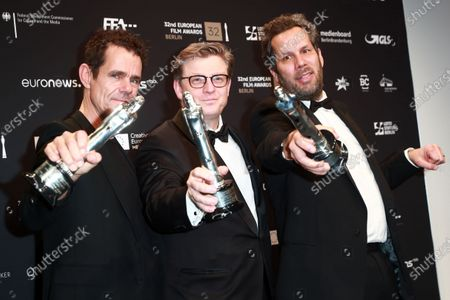 Stock Photo of Tom Tykwer, Henk Handloegten and Achim von Borries pose with their European Achievement in Fiction Award during a photo-call after the 32nd European Film Awards ceremony in Berlin, Germany, 07 December 2019.