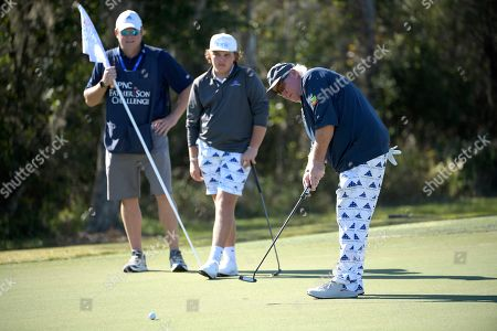Little John Daly, center, watches as his father, John Daly, right, putts on the seventh green during the first round of the Father Son Challenge golf tournament, in Orlando, Fla
