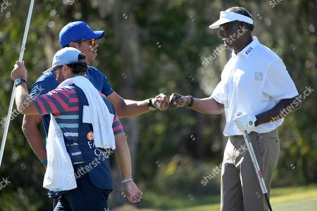 Vijay Singh, right, of Fiji Islands, is congratulated by his son, Qass Singh, after making a putt for birdie on the seventh green during the first round of the Father Son Challenge golf tournament, in Orlando, Fla