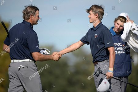 Retief Goosen, left, of South Africa, shakes hands with his son, Leo Goosen, after finishing on the 18th green during the first round of the Father Son Challenge golf tournament, in Orlando, Fla
