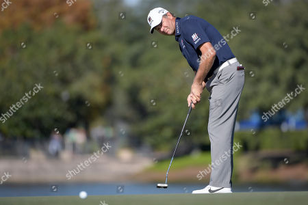 Retief Goosen, of South Africa, watches his putt on the 18th green during the first round of the Father Son Challenge golf tournament, in Orlando, Fla